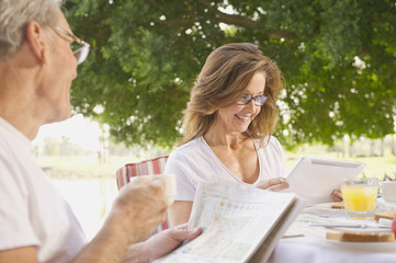Caucasian couple reading newspapers and enjoying breakfast together