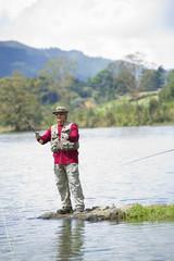 Hispanic man fishing in lake