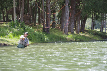 Hispanic man fishing in lake