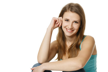 Smiling young woman sitting in front of a white background
