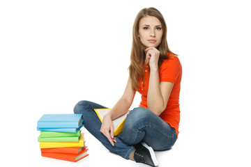 Calm woman sitting on the floor with stack of books