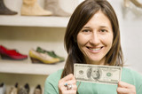 Hispanic woman holding cash in shoe store