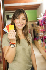Hispanic woman holding credit cards in store