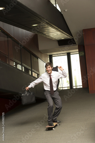 Hispanic businessman riding on skateboard