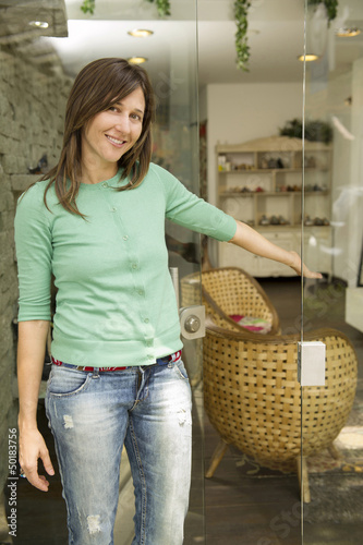 Hispanic woman standing in shop doorway