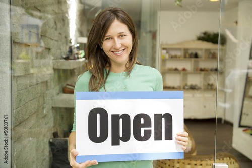 Hispanic woman holding open sign in shoe store