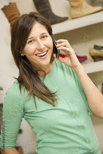 Hispanic woman talking on cell phone in shoe store