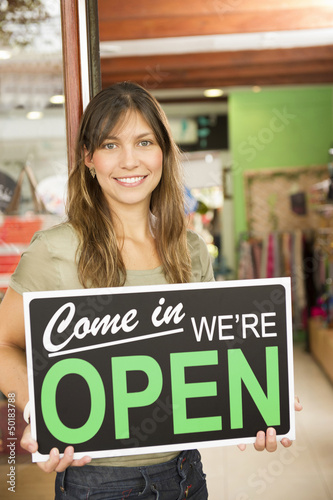 Hispanic woman holding open sign in store
