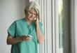 Caucasian surgeon in scrubs using cell phone