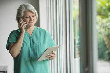 Caucasian surgeon in scrubs using cell phone and digital tablet
