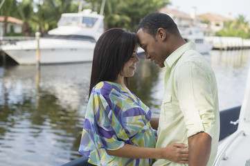 Mixed race couple hugging near waterfront