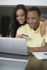 Mixed race couple shopping online with credit card