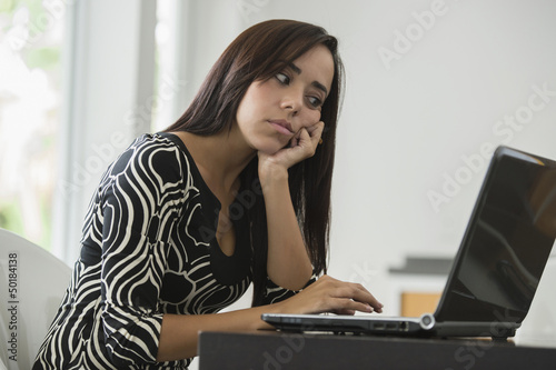Mixed race businesswoman typing on laptop