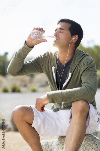 Mixed race man drinking water after exercise