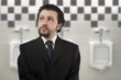 businessman with a distracted look urinating in urinals