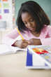 Black student writing in notebook in classroom