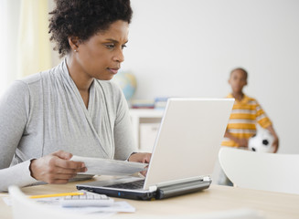 Black woman paying bills online with laptop