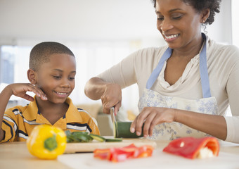 Black son watching mother slicing vegetables