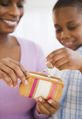 Black son putting coins into mother's purse