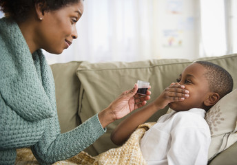 Black mother giving son cough syrup