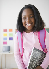 Black student holding notebook in classroom