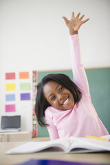 Black student raising arm answering a question