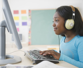 Black student using computer in classroom