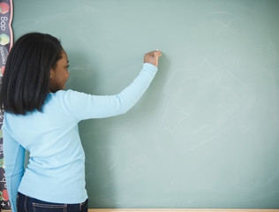 Black student writing on blackboard