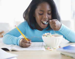 Black girl eating cereal and writing in workbook