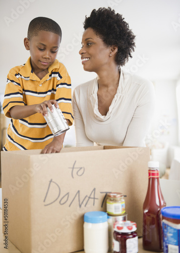 Black mother and son boxing food for donation