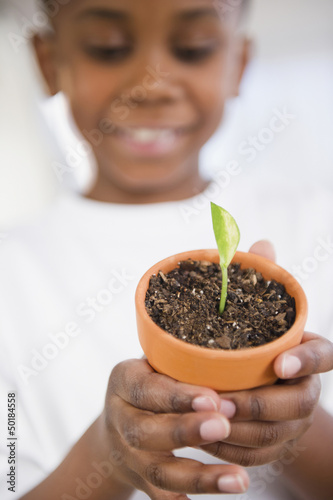 Black boy holding seedling in pot