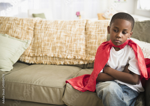 Pouting black boy in superhero cape