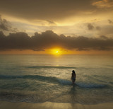 Hispanic woman wading in ocean at sunset