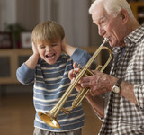 Caucasian boy listening to grandfather playing trumpet