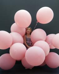 Caucasian girl holding large balloons