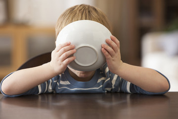 Caucasian boy eating from bowl