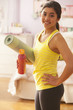 Mixed race girl holding water bottle and yoga mat