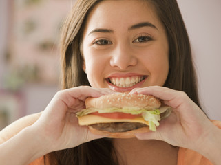 Mixed race girl eating hamburger
