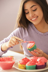 Mixed race girl frosting cupcakes