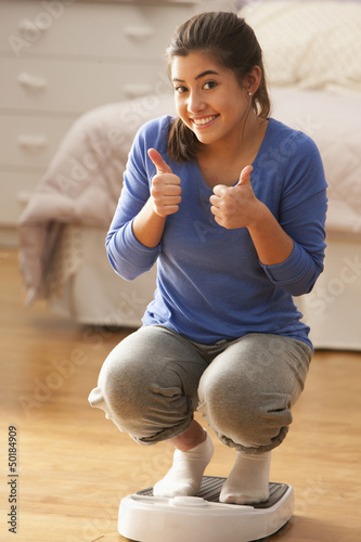 Mixed race girl on scale giving the thumbs up
