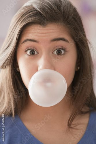 Mixed race girl blowing bubble
