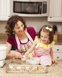 Caucasian grandmother and granddaughter baking cookies