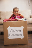 Caucasian boy donating clothing