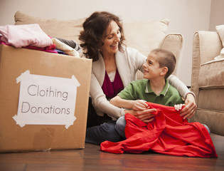 Caucasian grandmother and granddaughter donating clothing