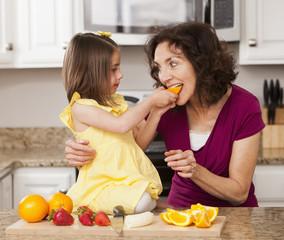 Caucasian grandmother and granddaughter eating fruit