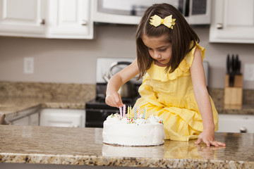 Caucasian girl putting candles on birthday cake