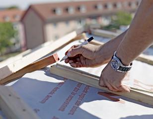 Dachdecker beim messen und anzeichnen