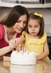 Caucasian mother and daughter lighting birthday candles