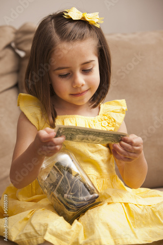 Caucasian girl putting money into jar
