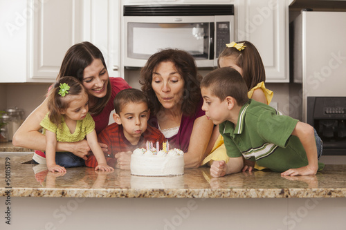 Caucasian family in kitchen blowing out birthday cake